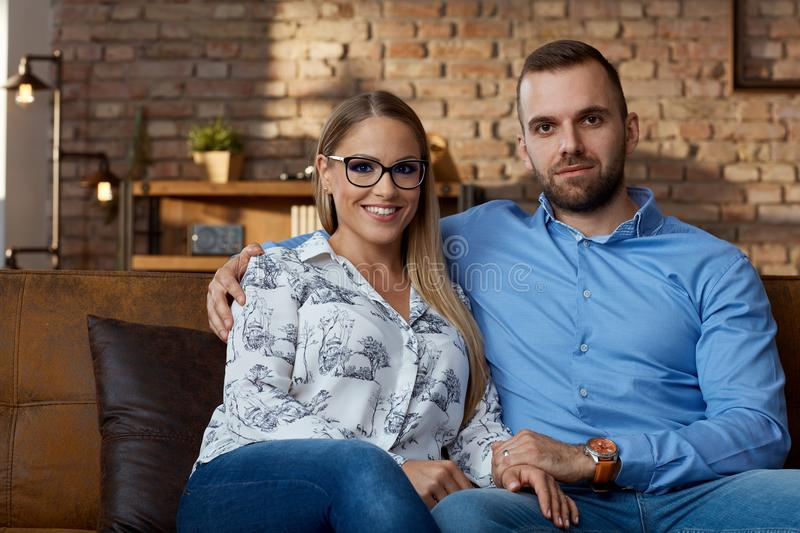 Happy young couple sitting on couch at home stock image
