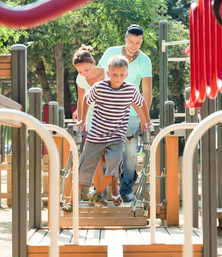 Couple together with teenager overcomes the obstacle course stock photos