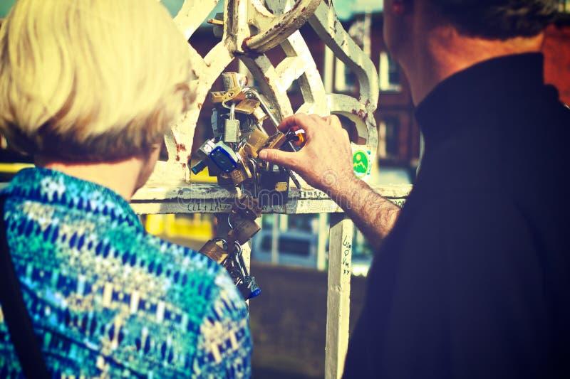 Couple touching padlocks together stock photos