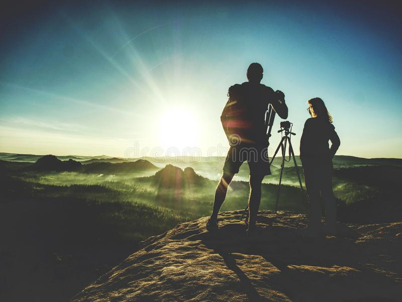 Couple tourist with photo camera at top of mountain watch sunset stock image