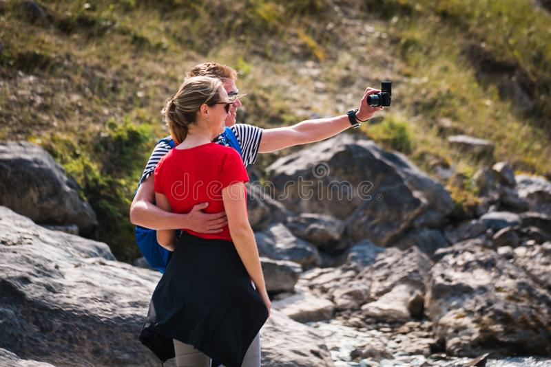A couple tourist taking there picture at Takkakaw Falls royalty free stock image