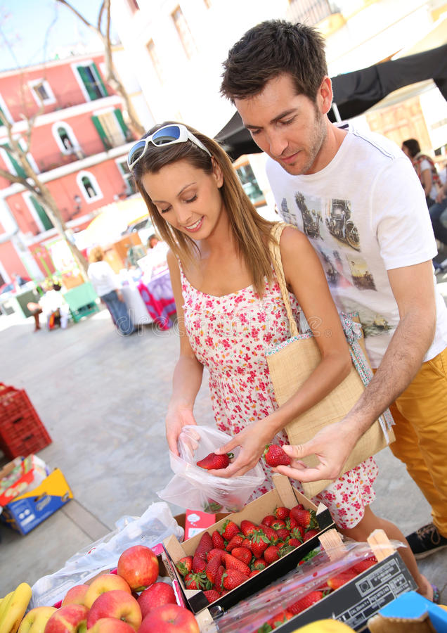 Couple of tourists buying strawberries on the market royalty free stock photo