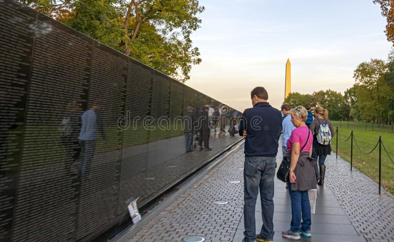 a couple of tourists contemplating the Vietnam Memorial Wall with the George Washington monument in the background royalty free stock photography