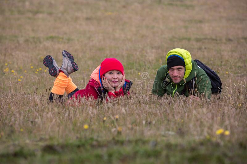 A couple of tourists, a girl in an orange jacket and a man in a green jacket, lie on a dry meadow royalty free stock photos