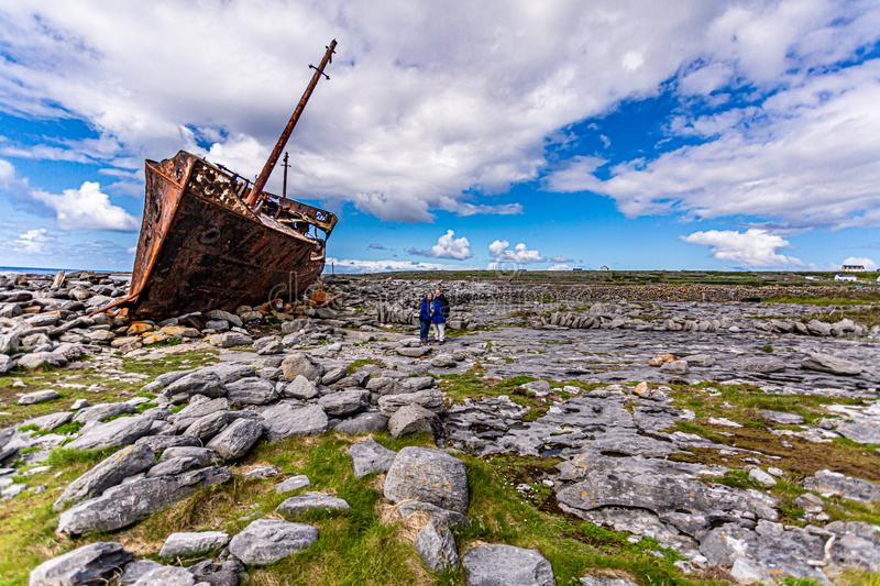 Couple of tourists next to the Plassey shipwreck on the stunning rocky beach of Inis Oirr island stock images