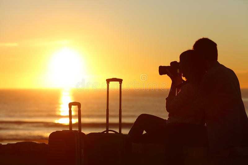 Couple of tourists photographing on holidays. Side view of a couple silhouette of tourists photographing the sun at sunset on the beach on holidays royalty free stock images