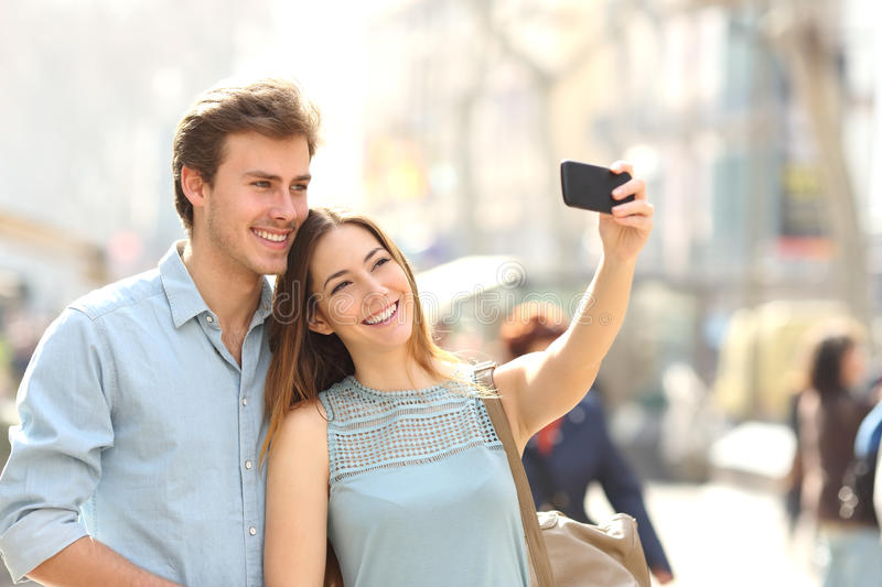 Couple of tourists photographing a selfie in a city street. Happy couple of tourists photographing a selfie in a city street in a sunny day stock photography