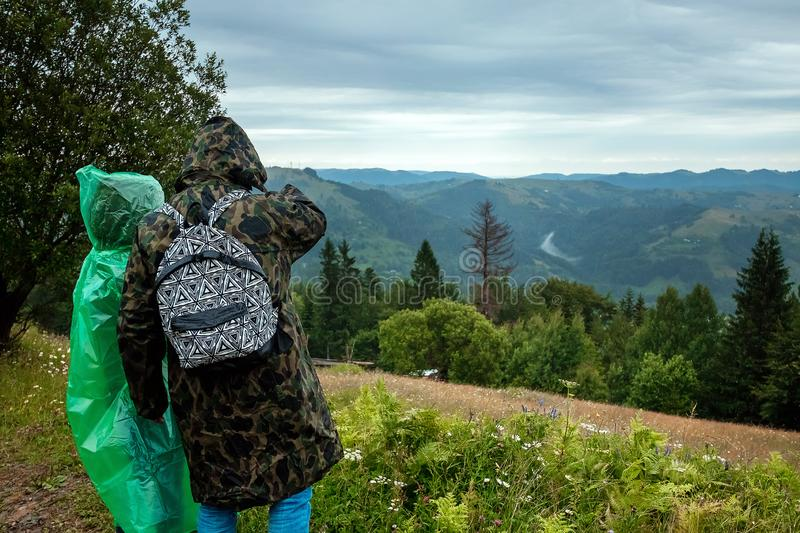 Couple, tourists in a raincoat on a background of beautiful Carpathian mountains. Rise in the mountains. Travel concept, leisure. Activity, vacation royalty free stock photography