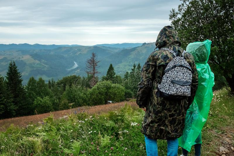 Couple, tourists in a raincoat on a background of beautiful Carpathian mountains. Rise in the mountains. Travel concept, leisure. Activity, vacation royalty free stock image
