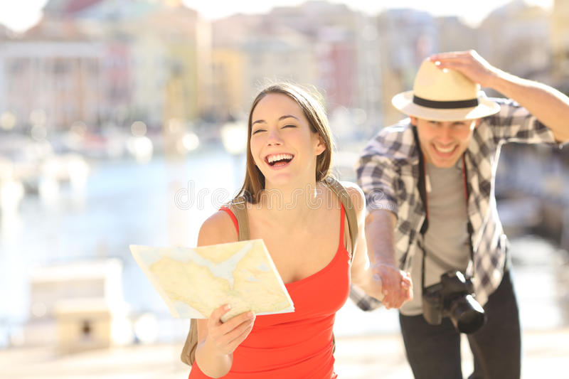 Couple of tourists running in travel destination. Front view of a happy couple of tourists running towards camera holding a paper map in a travel destination stock images