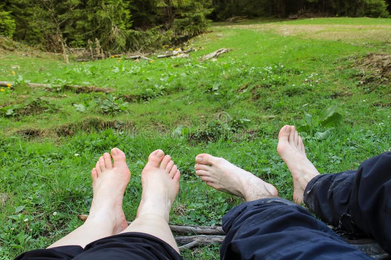 A couple of tourists slept and relaxed lying on the grass. Barefoot stock photos