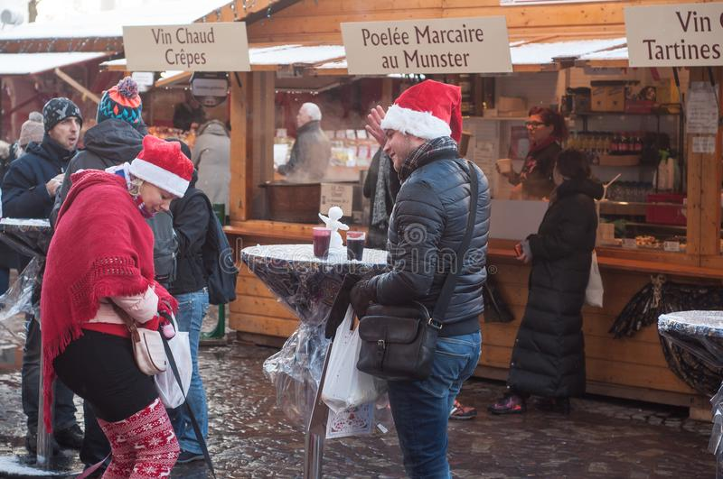 Couple of tourists smiling with christmas hats in the christmas market. Mulhouse - France - 10 December 2017 - couple of tourists smiling with christmas hats in royalty free stock photos