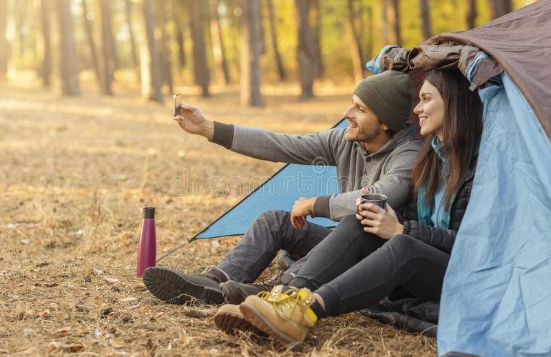 Couple of tourists taking selfie in camping tent royalty free stock images