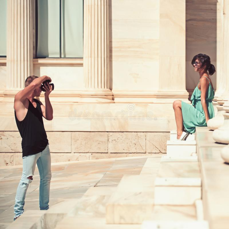 A couple of tourists visiting the Ancient Museum with man photographer and girl on stairs royalty free stock image