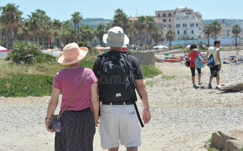 A couple of tourists walk on the beach under the blazing sun of an Italian summer. Summer A man and a woman with hats in the head to protect themselves from the royalty free stock photography