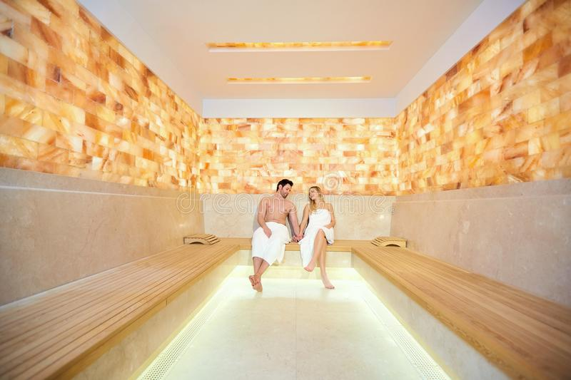 Couple in towels resting in the sauna. stock photography