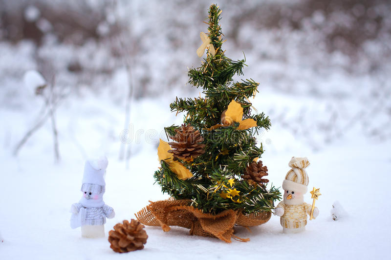 Couple of toy snowmen. Couple of snowmen in the winter woods near a Christmas tree stock photography