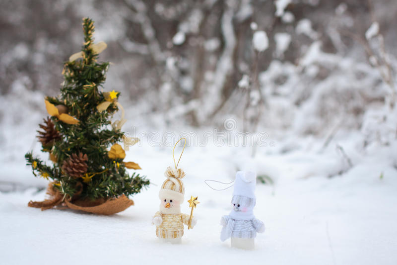 Couple of toy snowmen. Couple of snowmen in the winter woods near a Christmas tree royalty free stock photo