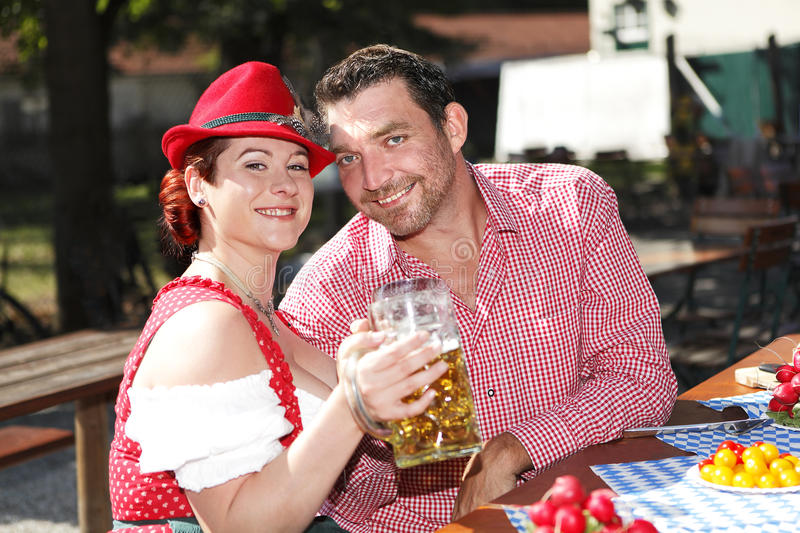 Couple in traditional costume in a beer garden stock photography