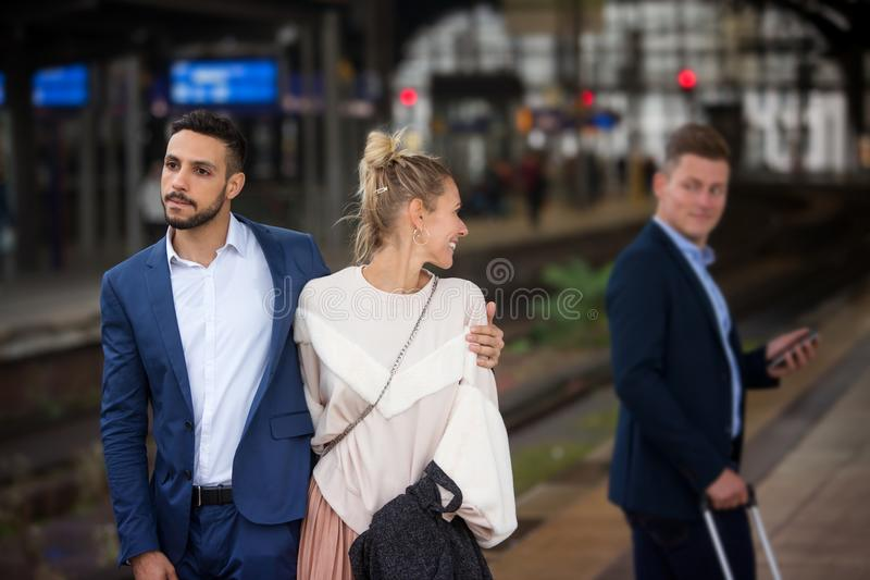 Couple at train station and woman flirting with another man. Couple walking at train station and women flirting with another man stock images
