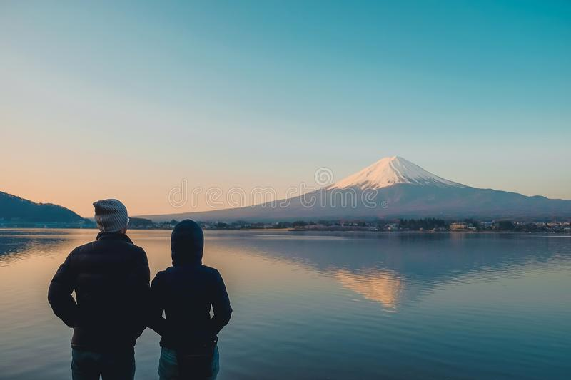 Couple traveler standing and looking Beautiful Mount Fuji with snow capped in the morning sunrise at Lake kawaguchiko, Japan. royalty free stock photography