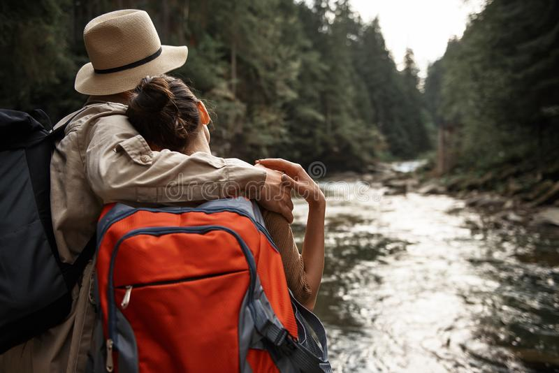 Couple of travelers hugging and looking at the trees and river flow stock photo