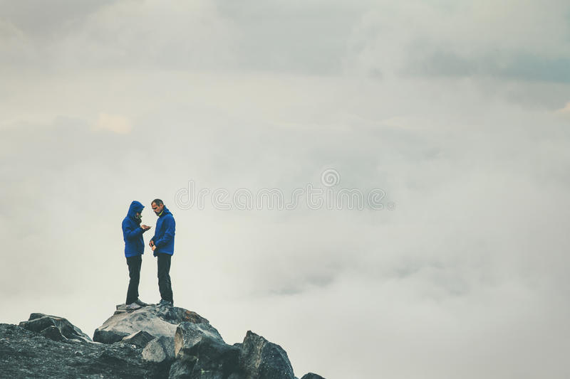 Couple Travelers in love standing on cliff together stock photos
