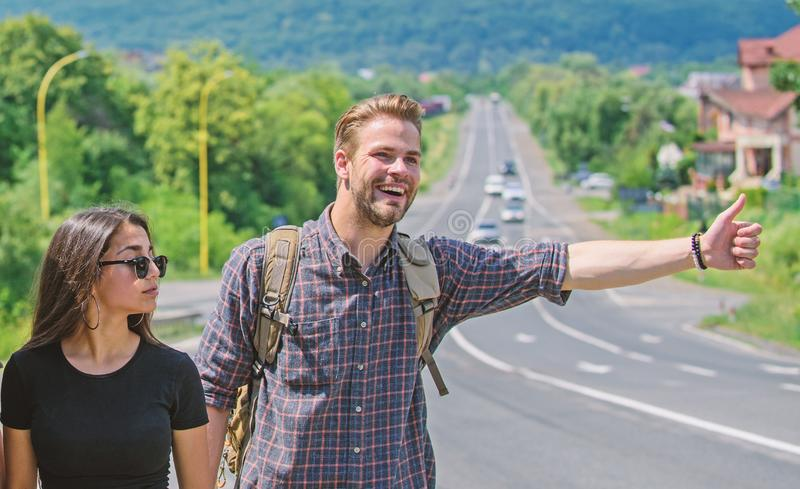 Couple travelers man and girl hitchhiking at edge road nature background. Travel by autostop. Couple hitchhikers. Couple travelers men and girl hitchhiking at stock photo
