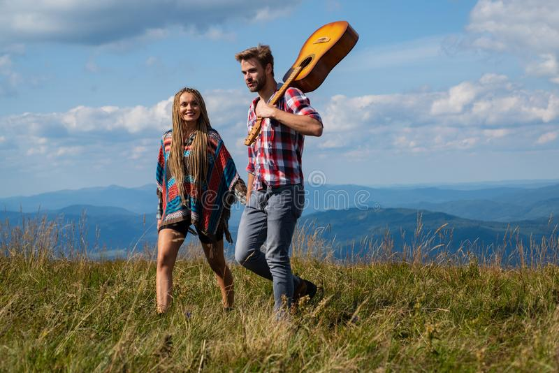 Couple travelers Man and Woman follow holding hands at sunny mountains landscape on background. Couple in love. royalty free stock image