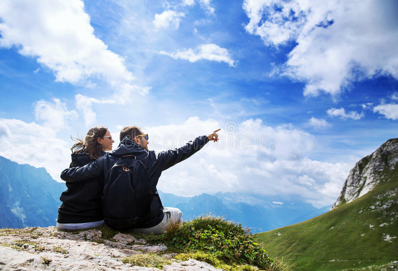 Couple of travelers on top of a mountain. Mangart, Julian Alps, Slovenia. stock photos