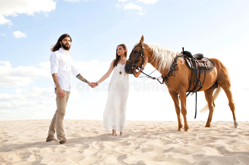 Couple of travellers holding hands, walking through desert on horse. Couple of travellers and lovers walking walking through desert on horse stock photos