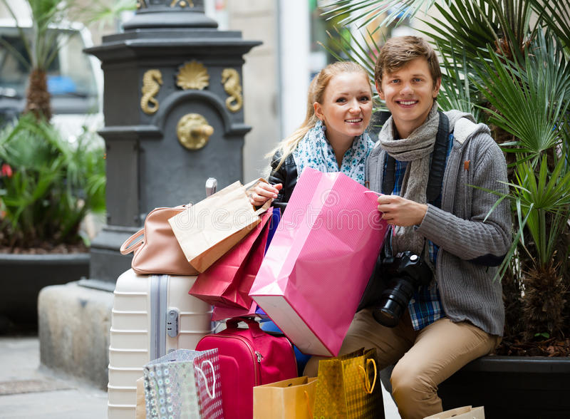 Couple of travellers with shopping bags stock photography