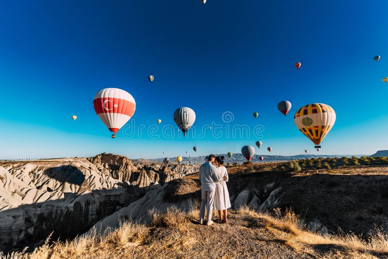 Couple travels the world. Happy and loving couple among balloons in Turkey. Married couple on vacation. Tourists in Cappadocia. royalty free stock photography
