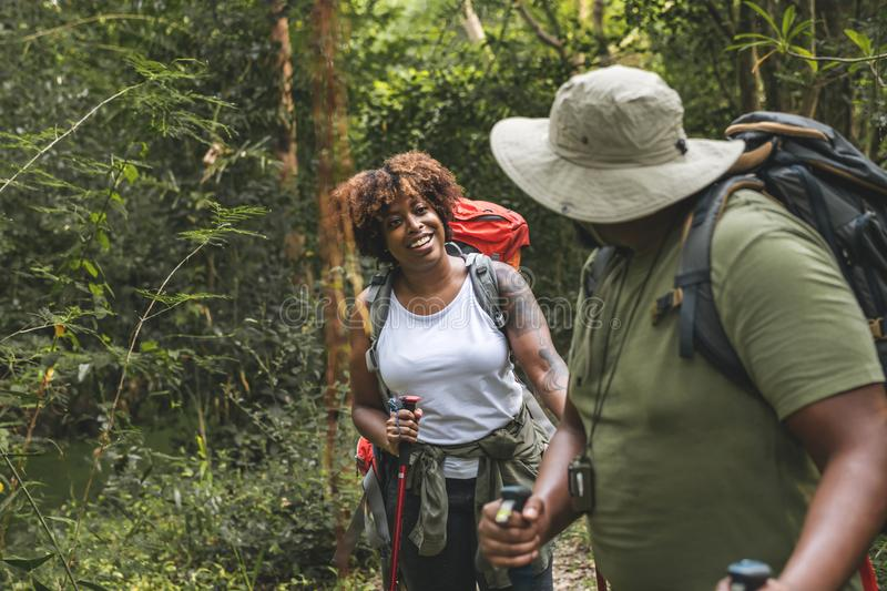 Couple trekking in the forest together stock images