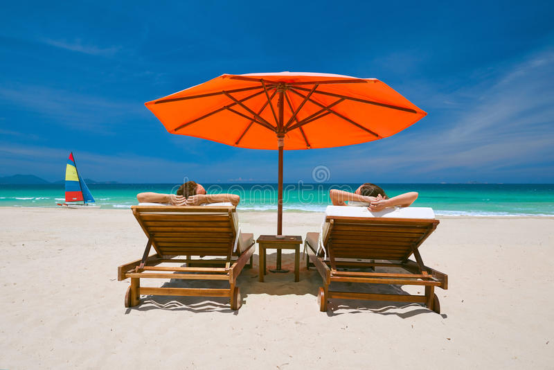 Couple on a tropical beach on deck chairs under a red umbrella royalty free stock images