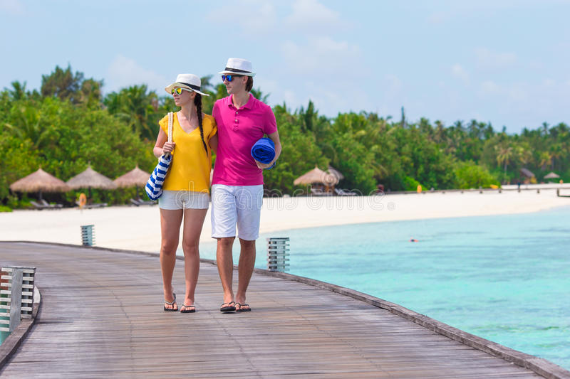 Couple on tropical beach jetty going to the beach royalty free stock photography