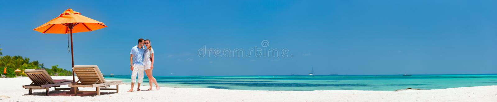 Couple at tropical beach. Romantic couple on a tropical beach during honeymoon vacation, super wide panorama perfect for banners royalty free stock photo