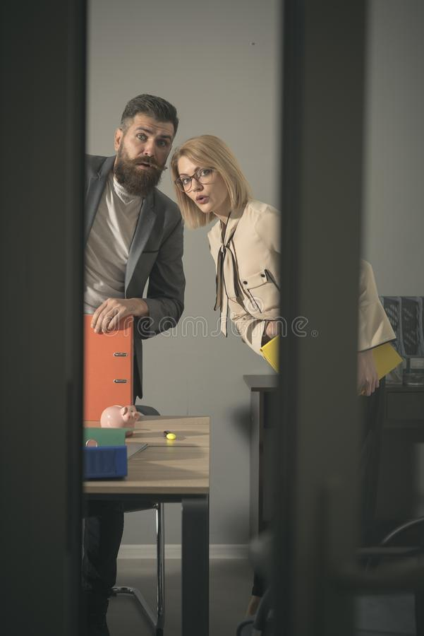 Couple with troubled faces look out modern office. Couple of colleagues at business meeting in office with glass walls stock image