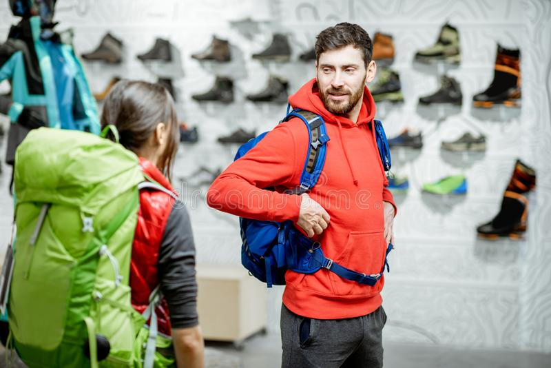 Couple trying backpacks in the sports shop stock images