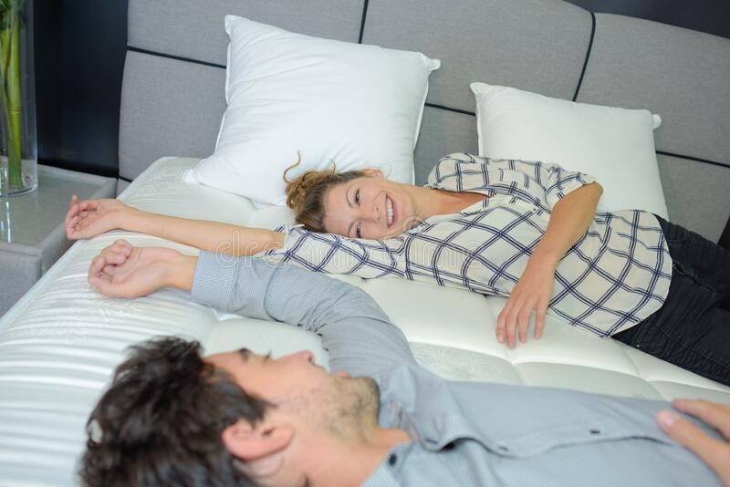 Couple trying new bed stock image