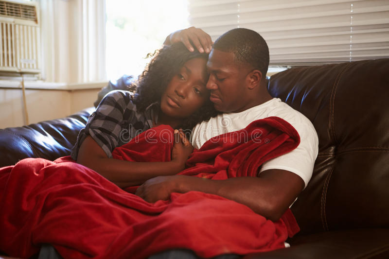 Couple Trying To Keep Warm Under Blanket At Home stock images