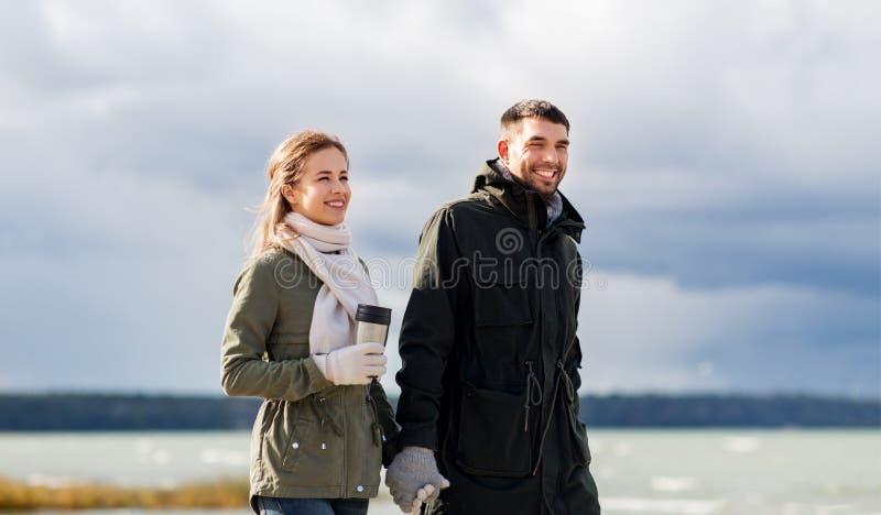 Couple with tumbler walking along autumn beach royalty free stock photo