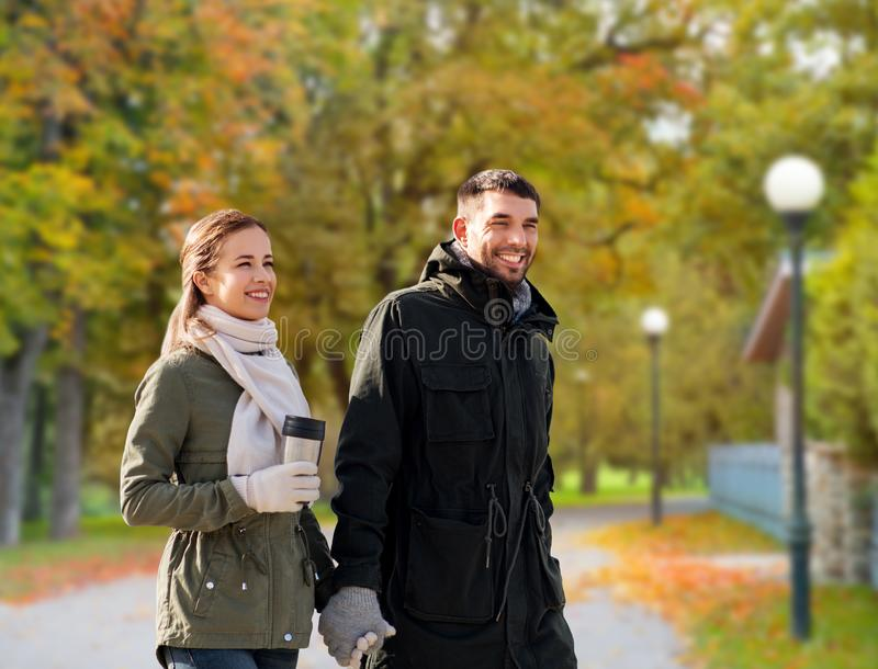 Couple with tumbler walking along autumn park royalty free stock image
