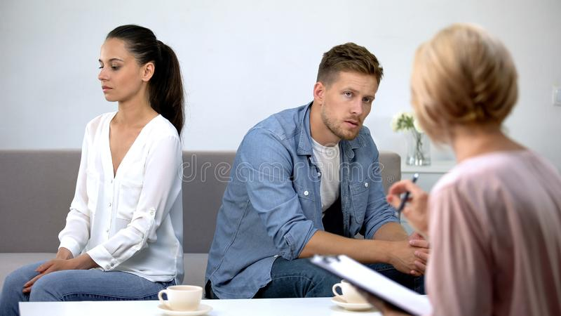 Couple turned from each other sitting at psychology therapy working on relations stock image