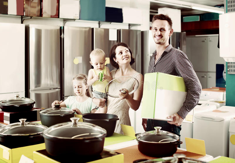 Couple with two children picking new kitchenware in home appliances shop. Smiling american couple with two children picking new kitchenware in home appliances royalty free stock images