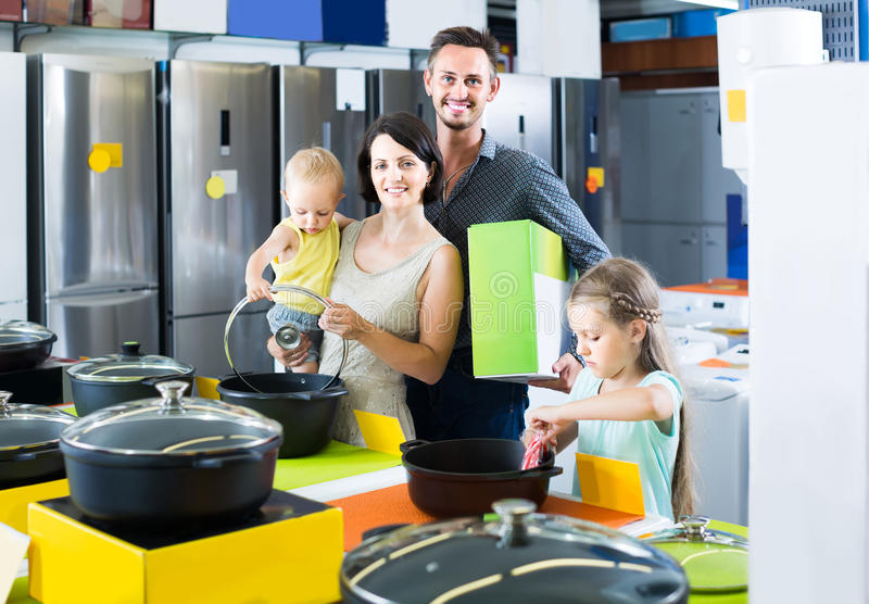 Couple with two children picking new kitchenware in home appliances shop. Smiling european couple with two children picking new kitchenware in home appliances stock image