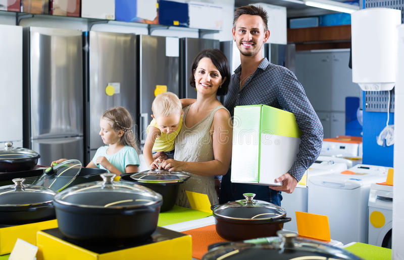 Couple with two children picking new kitchenware in home appliances shop. Smiling russian couple with two children picking new kitchenware in home appliances stock photography