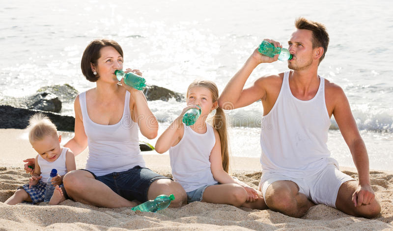 Couple with two kids drinking fresh water on sandy beach. Cheerful couple with two kids drinking fresh water on sandy beach stock photography