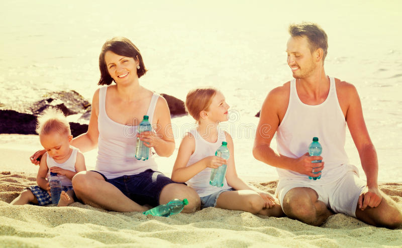 Couple with two kids drinking fresh water on sandy beach. Cheerful american couple with two kids drinking fresh water on sandy beach royalty free stock images