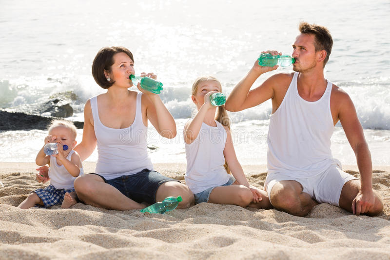 Couple with two kids drinking fresh water on sandy beach. Cheerful spanish couple with two kids drinking fresh water on sandy beach stock image